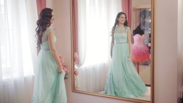 Boldog asszony néz a tükörbe, megcsodálta a kiválasztott ruha és fonó