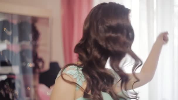 hezká žena v krásné šaty a účes pózuje v zrcadle