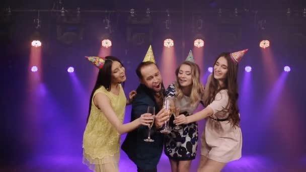 Skupina přátel s sklenic šampaňského v nočním klubu vystupují