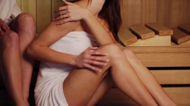Mladých ženách v bílém ručníku péče o nohy sedící v sauně