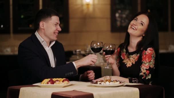 usmívající se pár cinkání sklenic vína během oběda v restauraci