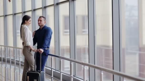portrét mladého šťastnému páru s zavazadel na letišti při pohledu na sebe