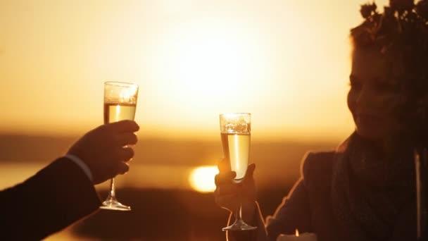 Pár na romantické rande v restauraci na pláži při západu slunce