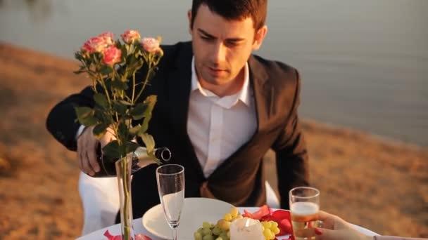 Kerl gießt Champagner in ein Glas. Romantisches Date im Strandrestaurant bei Sonnenuntergang