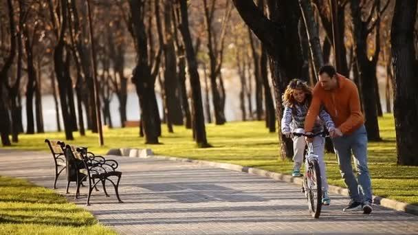 Mladí a radostné pár naučit se jezdit na kole a vzducholoď na něj v parku