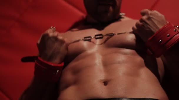 muscular body of a stripper. Handcuffs and a blade sliding on a naked torso.