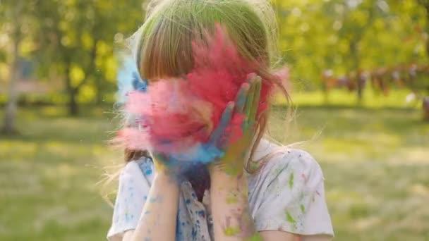 Porträt eines süßen Mädchens in den Farben des Holi-Festes.
