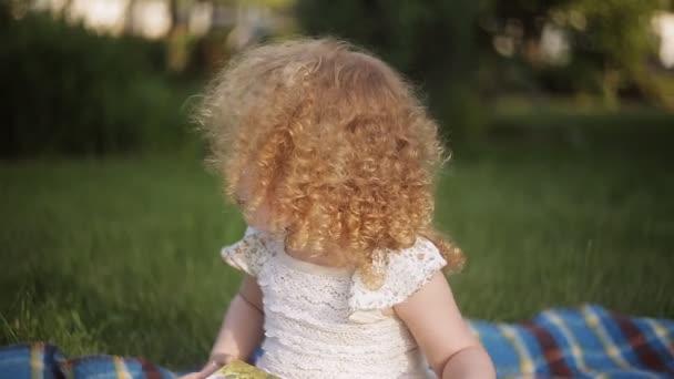 malá holčička čtení knihy v parku na jaře, tónování fotografií