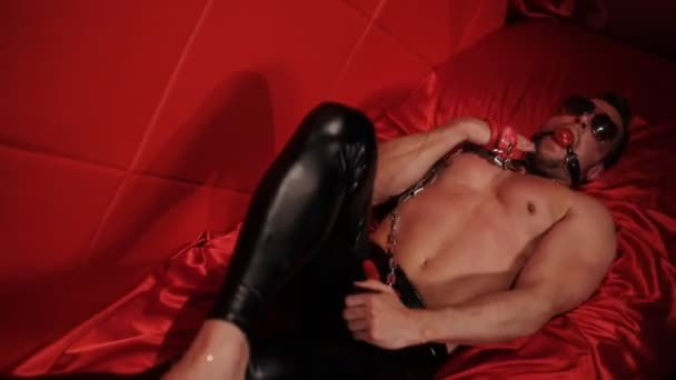 The male stripper in womens shoes, with a gag in his mouth is in the red room