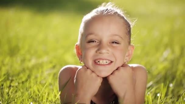 Malá holčička při západu slunce na trávu a usmívá se na kameru