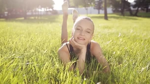 Smiling Girl lying on Green Grass and smiling. A young gymnast in the grass.
