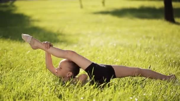 Petite flexible girl does in the grass complex gymnastic exercises.