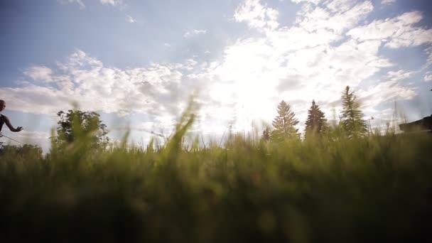 Lány tornász, a háttérben a jumping szalaggal napnyugtakor ég.