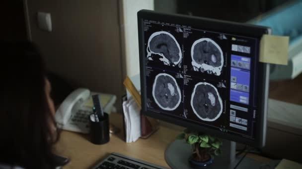 Ärztin Radiologenanalyse medizinische Bildgebung auf Computermonitor.