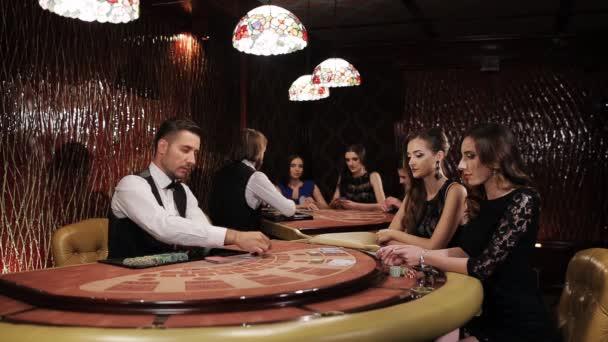 Dvě krásné ženy hrají na tabulka Blackjack v kasinu