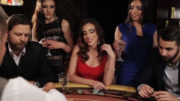 Skupina mladých a krásných lidí pití šampaňského a hraje blackjack