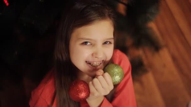 Zwei kleine Schwestern schmücken den Weihnachtsbaum mit Tannenzapfen. Neujahrsvorbereitung. glückliche Mädchen und Familie.