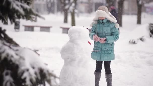 Dívka modeluje sněhulák na sněhu v zimě.