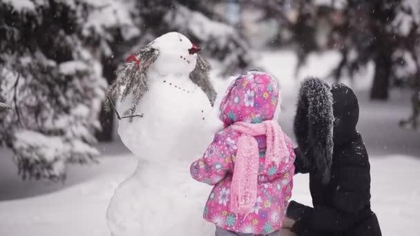 rodiče a děti si hrají ve sněhu. Máma a dcera vyřezávat ze sněhu v zimě lese.