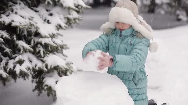 Mädchen modelliert im Winter einen Schneemann im Schnee.