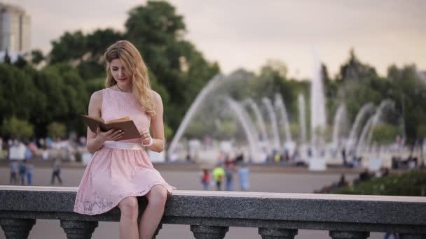 mladá atraktivní dívka v letním parku kašna čte knihu se zájmem