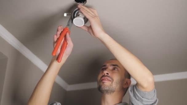 Samec elektrikář pracuje s kleštěmi při instalaci stropních světel.