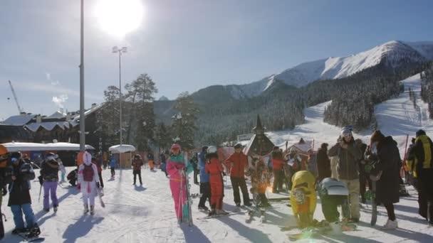 Russland. Arkhyz. Januar 2021. Romantisches Skigebiet. Das zentrale Gebäude des Dienstleistungszentrums im Skigebiet. Menschen auf Skiern und Snowboards auf den Pisten des Skigebiets.