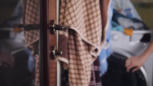 Dívka vloží ručník do pračky a otevře dveře, aby se dostala z koupelny, zblízka kliky dveří.