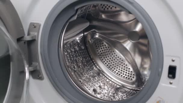 Ein Mädchen legt schmutzige Dinge in die Waschmaschine, Nahaufnahme.