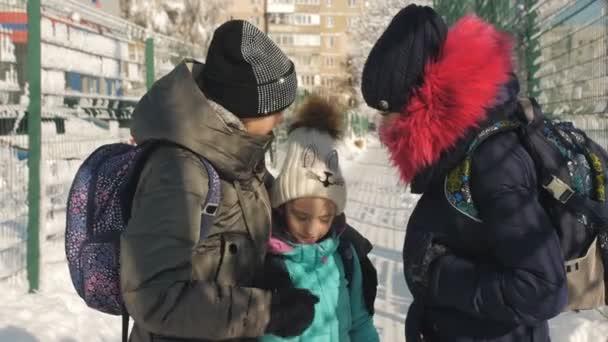Egy téli iskoláslány télen télikabátban és kalapban egy barátjával elviszi a húgát az iskolába egy napos havas napon..