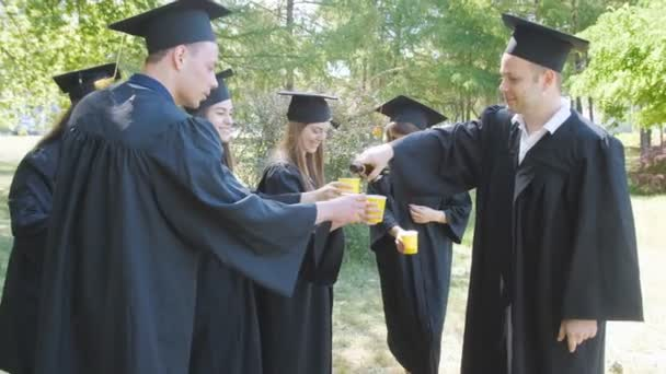 Happy graduate students in black graduation robes celebrate their graduation with champagne.