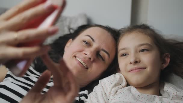 A happy woman and her daughter lie together on a bed, take selfies on a smartphone, or communicate via video link with their father or grandmother.