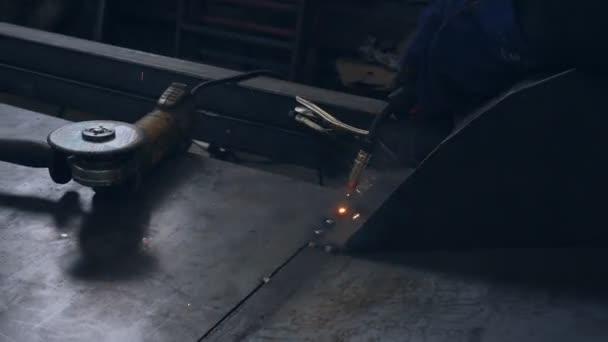 Svářečka v ochranné masce v autoopravně přivařuje ke dnu vozu kovový plech.