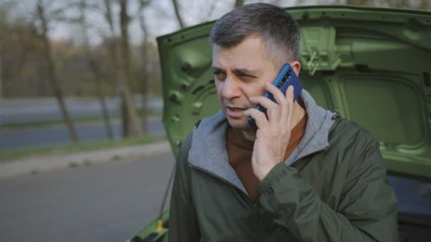 Das Konzept einer Autopanne auf dem Weg. Ein Mann bittet um technische Hilfe am Telefon, aus nächster Nähe.