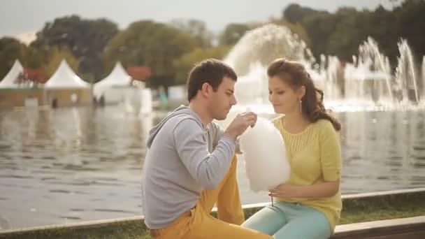 milující pár v parku jíst cukrovou vatu