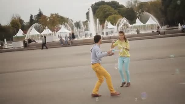 mladý pár se baví v parku s mýdlové bubliny
