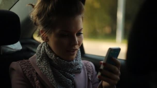ragazza cavalca in un taxi e guardando al telefono