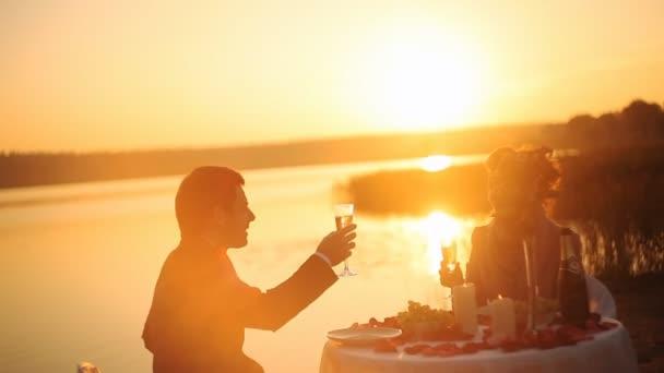 Coppie che ripartono romantica cena al tramonto sulla spiaggia