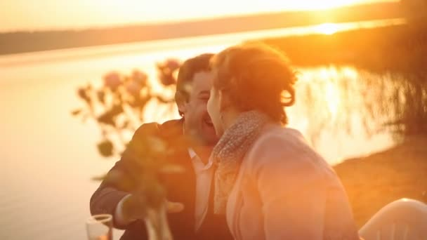 Muž políbil ženu na pláž sunset. Piknik s vínem