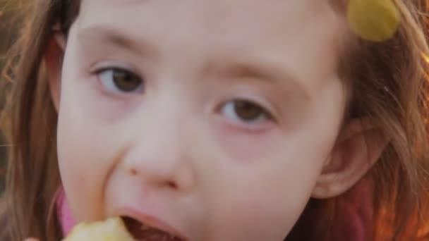 malá holčička jíst jablko při západu slunce. detail