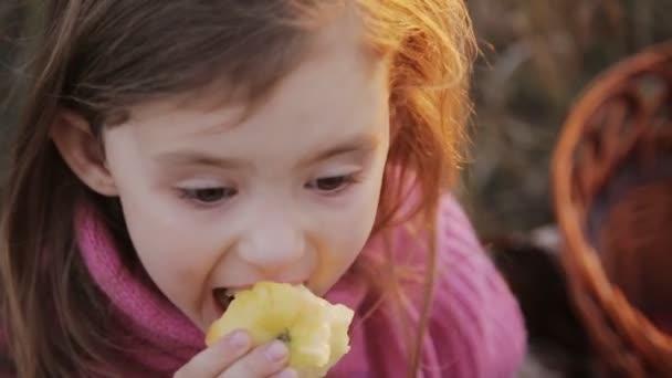 malá holčička jíst jablko v přírodě