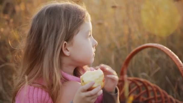 a little girl eating an apple at a picnic