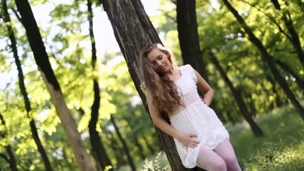 szexi lány a fehér ruhában a táncot a fa az erdő