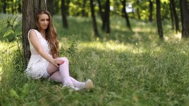 Sexy dívky v bílých šatech sedící proti strom v trávě