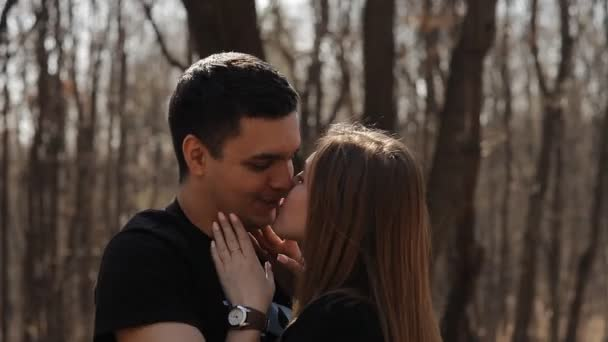 man and woman in a spring forest park kiss