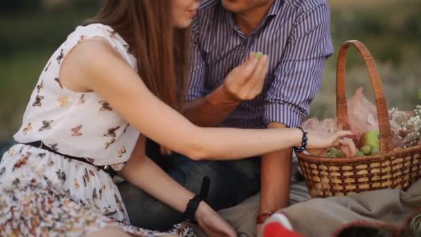Mladý pár jíst hrozny na pikniku na slunečný den