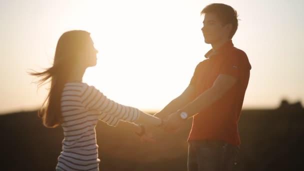 ein hübscher junger Kerl dreht das Mädchen auf die Hand