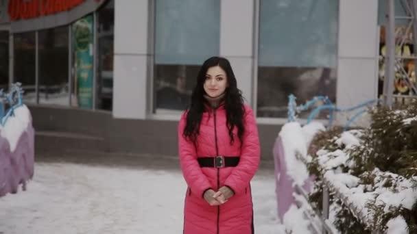 krásná dívka chodit v zimě uličce na pozadí budovy