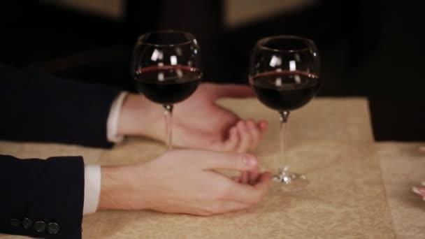Hände Mann und Mädchen auf dem Hintergrund von Gläsern mit Wein