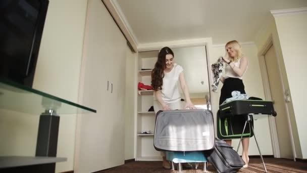 dvě sestry shromažďovat věci v kufru v hotelovém pokoji